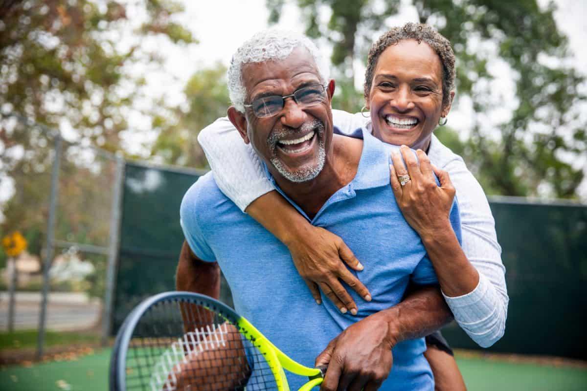 A senior black couple piggyback together on the tennis court