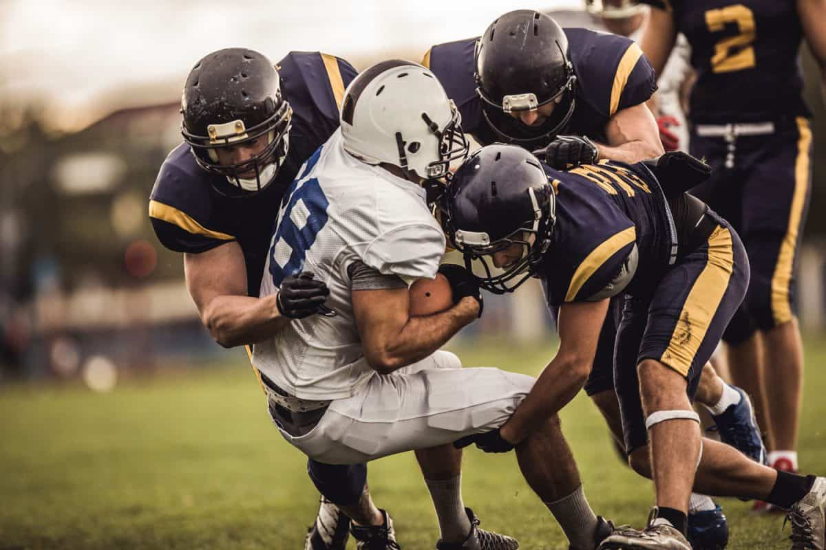 American football players tackling opposite's team quarterback during the match