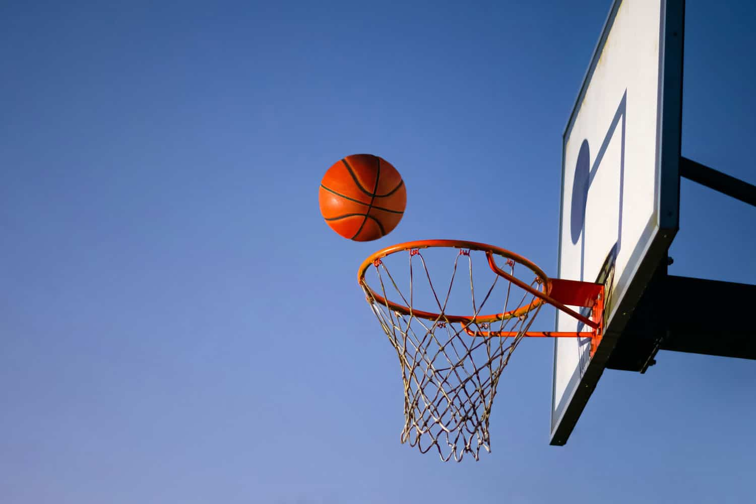 Close up of orange ball above the hoop net with blue sky in the background