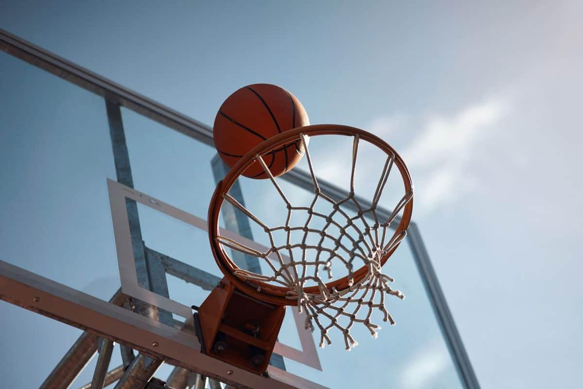 Closeup shot of a basketball landing into a net on a sports court