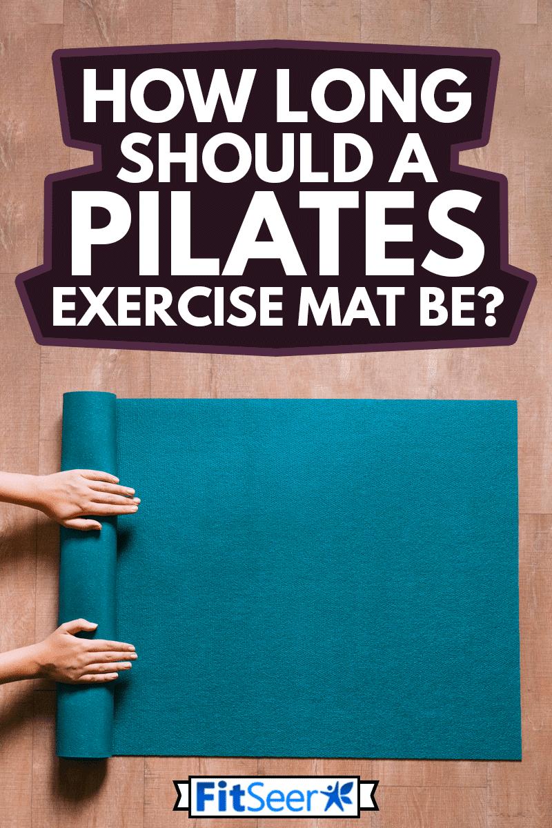 Woman folding blue pilates mat on wooden floor, How Long Should A Pilates Exercise Mat Be?