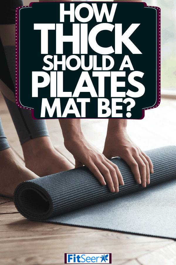 A woman rolling up her pilates mat inside her living room, How Thick Should A Pilates Mat Be?