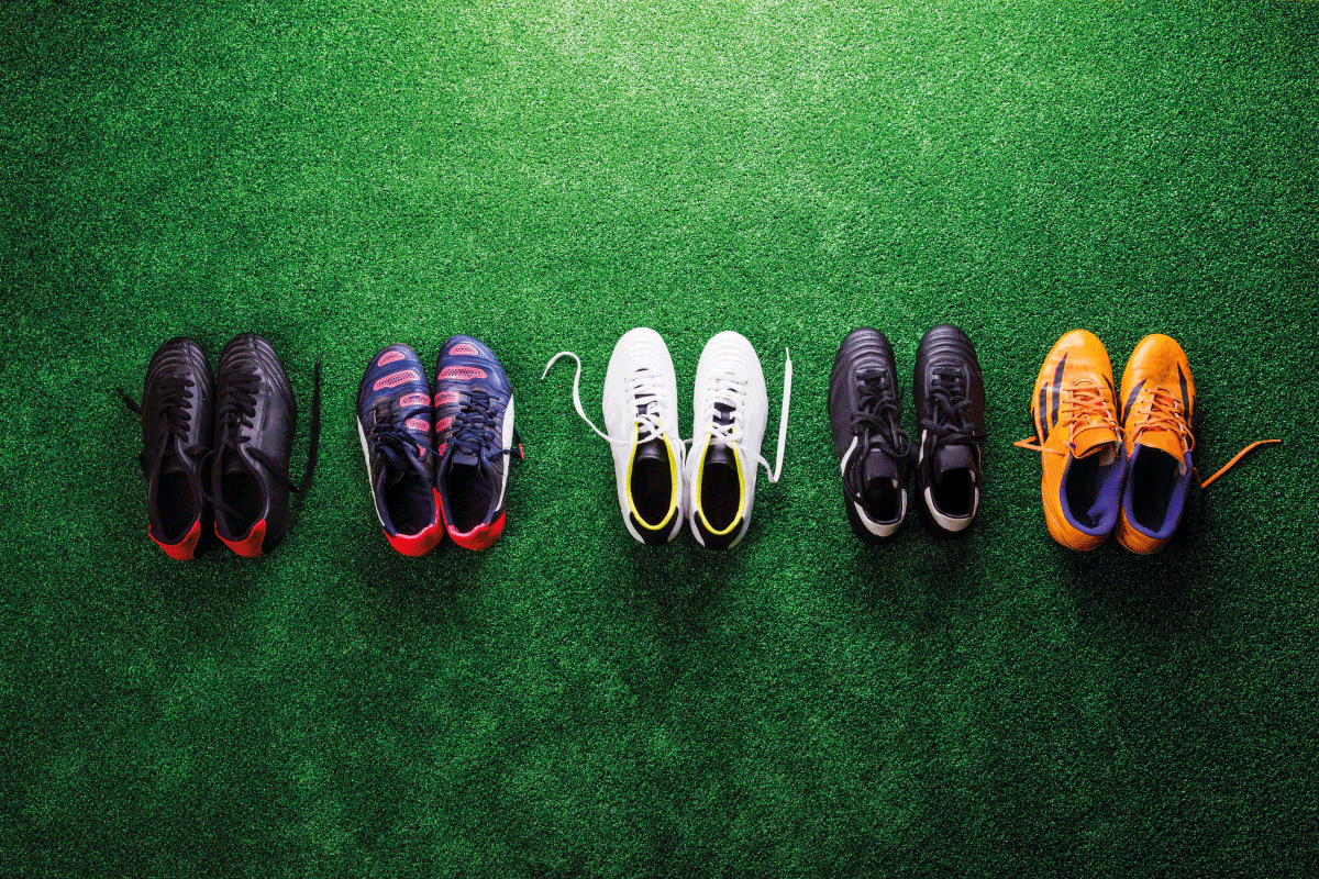 Various colorful cleats against artificial turf. Football Vs Lacrosse Cleats—The Key Differences